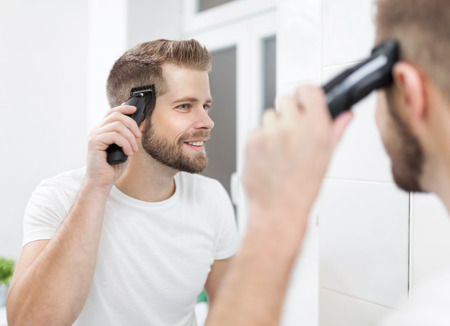 Handsome bearded man cutting his own hair with a clipper Фото со стока