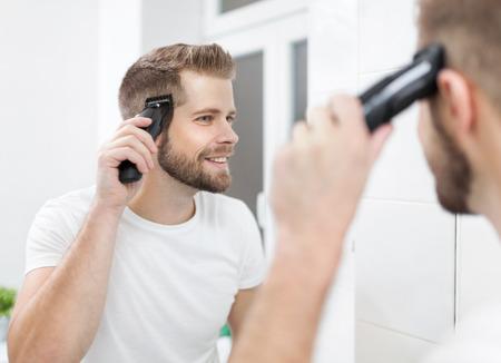 Uomo barbuto bello che taglia i suoi capelli con una tosatrice Archivio Fotografico