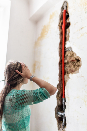 Woman looking at damage after a water pipe leak at home Imagens - 105728231