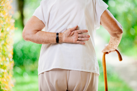 Elderly woman outdoors with lower back pain Standard-Bild
