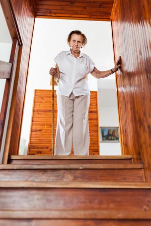 Femme âgée à la maison à l'aide d'une canne pour descendre les escaliers