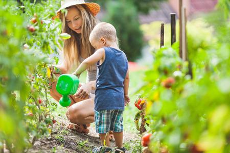 Niño lindo ayudando a mamá en el jardín