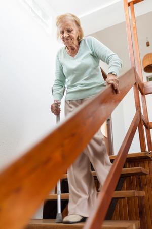 Anciana en casa con un bastón para bajar las escaleras Foto de archivo