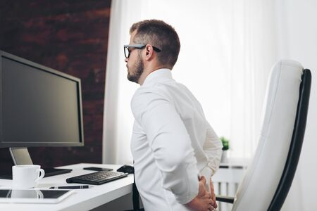 Office worker with back pain from sitting at desk all day Stock Photo