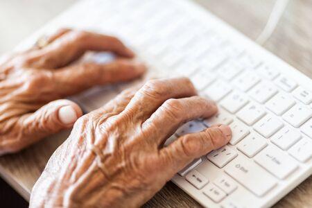 Elderly woman typing on a PC keyboard