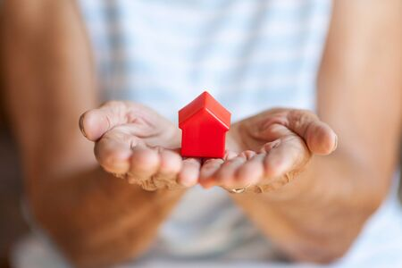 Elderly woman holding a small house in her hands Stock Photo