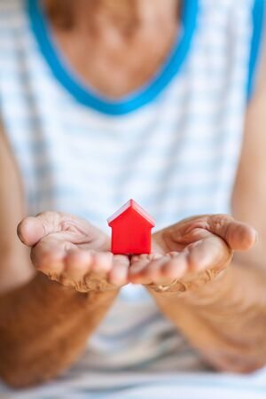 Elderly woman holding a small house in her hands Banco de Imagens