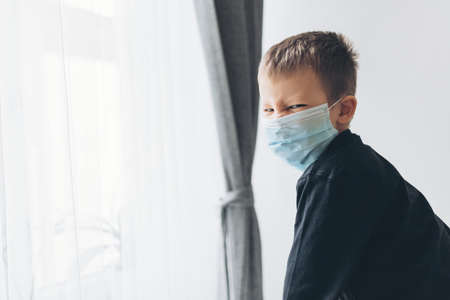 Unhappy young child wearing respiratory mask as prevention against the Coronavirus Covid-19 Imagens