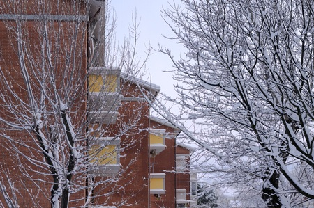 Brick building background and snowy park (Pesaro, Italy)