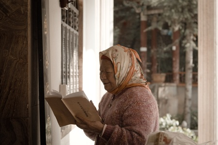 Kunming, Yunnan, China - 28 December 2017: An old woman is praying in the Yuantong Temple