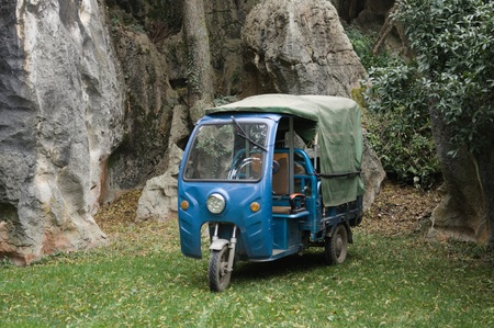 Blue three-wheeled transport vehicle in the Stone Forest (Kunming, Yunnan, China) Imagens