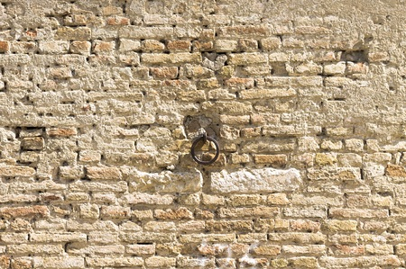 Isolated iron handle in a medieval wall background (Marche, Italy, Europe) Stock Photo