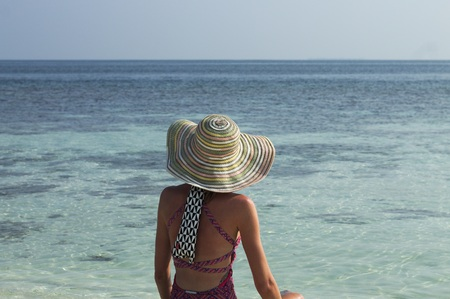 Girl with a straw hat and a swimsuit in a desert island (Ari Atol, Maldives, Asia)