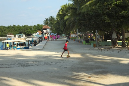 Ari Atoll, Maldives - 22 December 2018: A little boy is playing football in the harbor Editorial