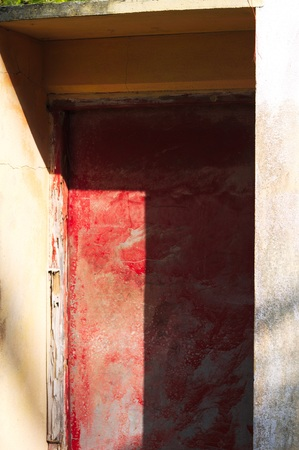 Red closed door of a dirty house