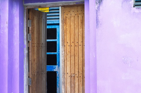Entrance of a violet house with a wooden door (Ari Atoll, Maldives)