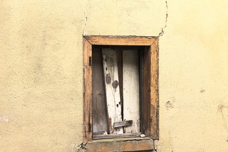 Isolated ruined window in a yellow wall (Bacharach, Germany, Europe)