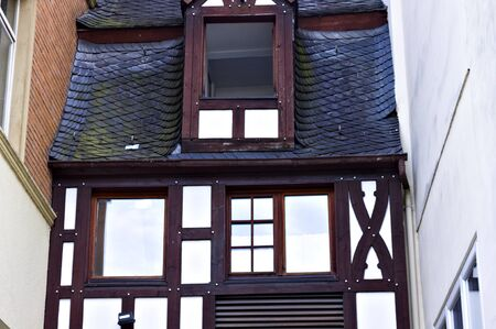 Half-timbered house with particular windows and black roof tiles