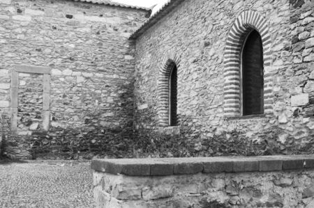 A couple of rounded arched windows of medieval building with bricks