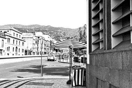 Funchal, Madeira, Portugal - August 16, 2019: A striped umbrella of food market in the corner of the street