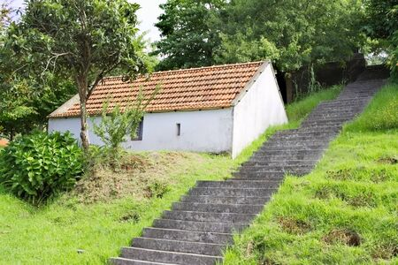 A white house near concrete stairs in a green park (Madeira, Portugal)