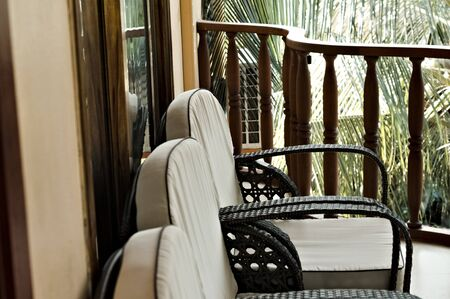 A series of white vintage chairs in the balcony (Ari Atoll, Maldives)
