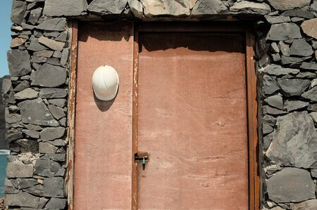 White worker with helmet hanging on a wooden door near the Atlantic Ocean