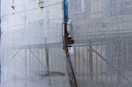 Dettaglio di un'impalcatura arrugginita attraverso una rete in fibra di plastica bianca