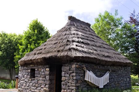 Old house of Santana in Madeira Island made of stones with a thatched roof. Some white clothes are hanging on the wall. (Santana, Madeira, Portugal) Stock Photo