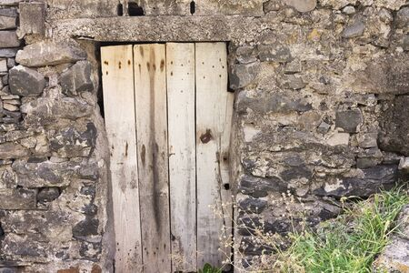 Isolated old wooden door in a rural place (Madeira, Portugal, Europe)