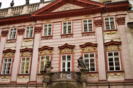 Old pink bohemian building with columns and red decorations (Prague, Czech Republic, Europe) Imagens