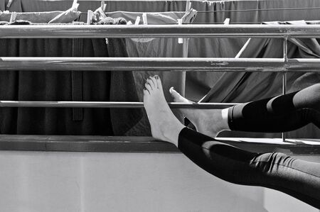 A woman with leggings and nail polish on toenails is relaxing in the balcony near towels hanging on a clotheshorse (Italy, Europe) Archivio Fotografico