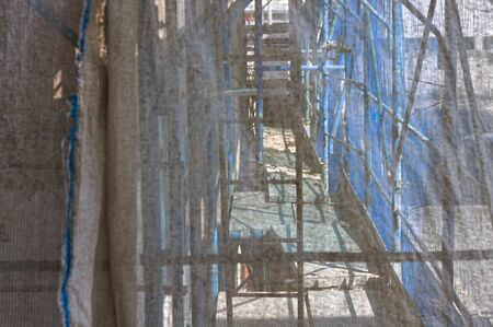 View of scaffoldings through a shielding sheet on a building site (Pesaro, Marche, Italy) Archivio Fotografico