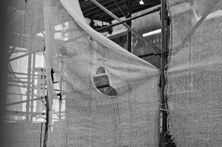 A broken scaffolding protection net in a building site (Pesaro, Marche, Italy) Archivio Fotografico