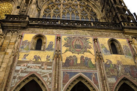 Prague, Czech Republic - December 28, 2019: Exterior details of St. Vitus Cathedral, a gothic religious building with towers, spires and mosaic decorations Editorial