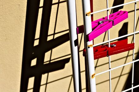 A pair of red and fuchsia clothespins attached to the clothe horse against the wall