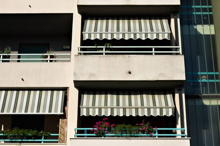 Building with a series of balconies with striped awnings (Pesaro, Italy, Europe)