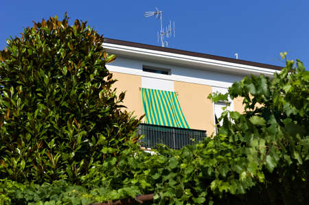 A green and yellow striped sun awning of a building hidden by plants and trees (Pesaro, Italy, Europe)