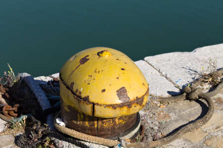 A yellow mooring bollard with a mooring rope on the harbor pier (Pesaro, Italy, Europe)