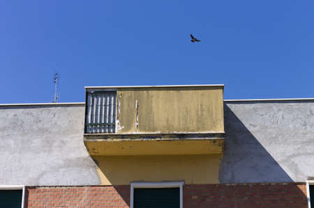 A bird is flying above an old ruined balcony of an abandoned building (Pesaro, Italy, Europe)