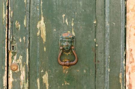 Decorated iron door knocker of a green ruined door (Pesaro, Italy, Europe)