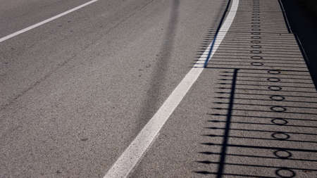 The shadow of a steel fence on the asphalt (Pesaro, Italy, Europe)