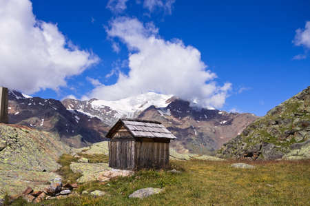 An isolated wooden shed with snowy mountains in background in the italian Alps (Trentino, Italy, Europe)