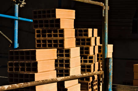 Hollow construction bricks stacked on a construction site on the scaffoldings (Pesaro, Italy, Europe)
