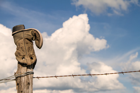 A cowboy boot upside down on a fence post in rural Kansas along a prairie with clouds in the background. Banco de Imagens