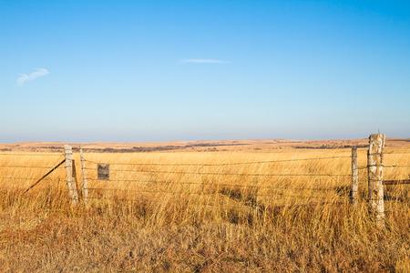 カンザス州の燧石の丘の草原の鉄線フェンス サインオン プレーリー祝福。 大草原は、農家と牧場主中西部の真の祝福です。