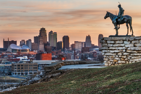Kansas City, Missouri, USA on March 22, 2014.  A image of the Kansas City Scout overlooking Kansas City at sunrise.  The Indian Scout is known as a Kansas City landmark and symbol of the city. The scout overlooks the Kansas City Skyline.