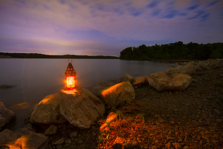 onto: Blue Springs Lake located outside of Kansas City, Missouri at night with a lantern glowing light onto the rocky shoreline