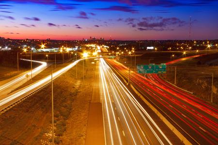 horizontal: A view of I-70 Interstate leading into Kansas City, Missouri at twilight. Stock Photo
