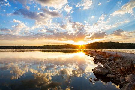 カンザスシティ、ミズーリ州の外の湖の上の岩の桟橋に沿って劇的な日の出。